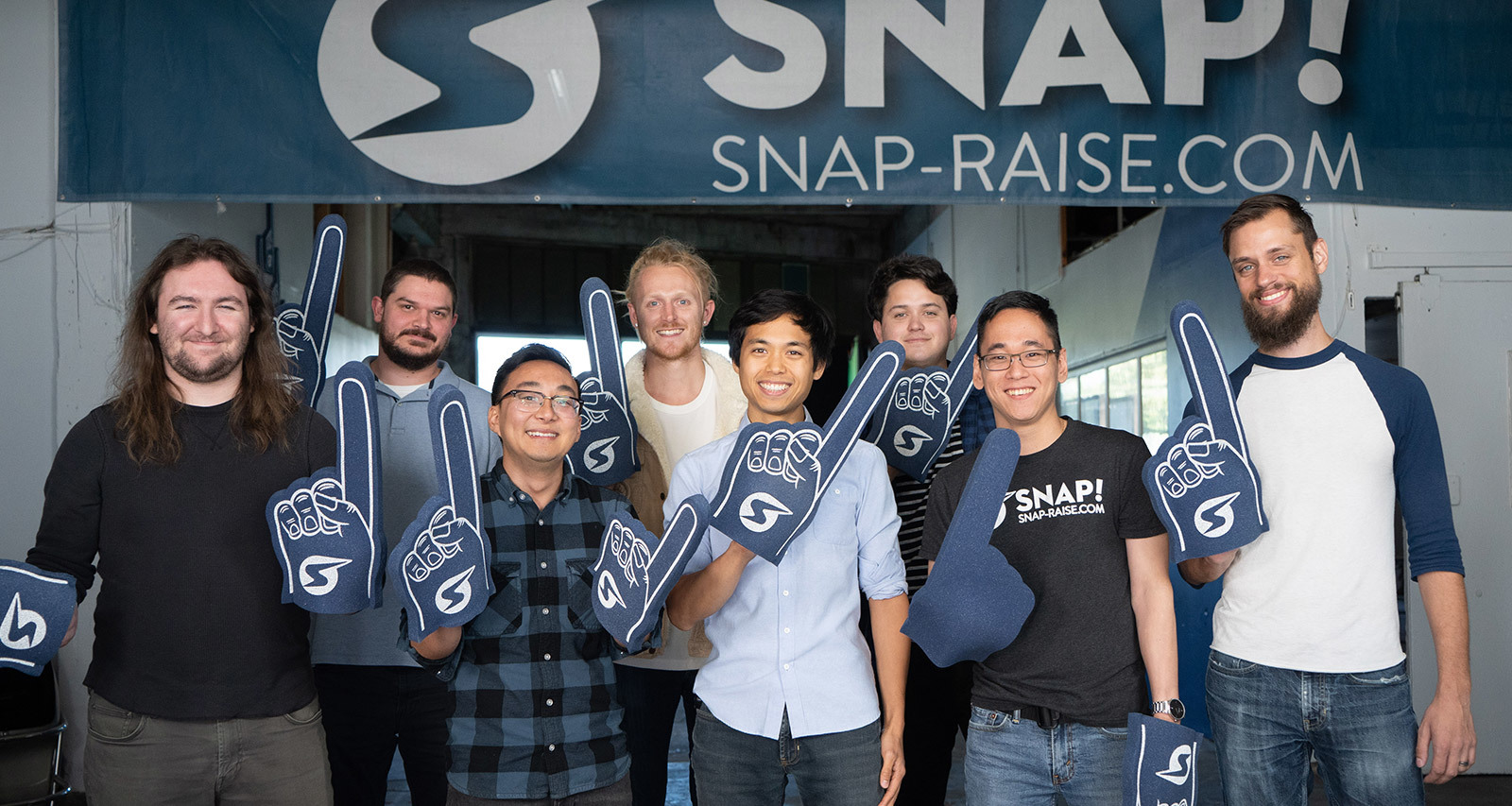A group of smiling Snap! Raise employees wear and wave spirt gear.