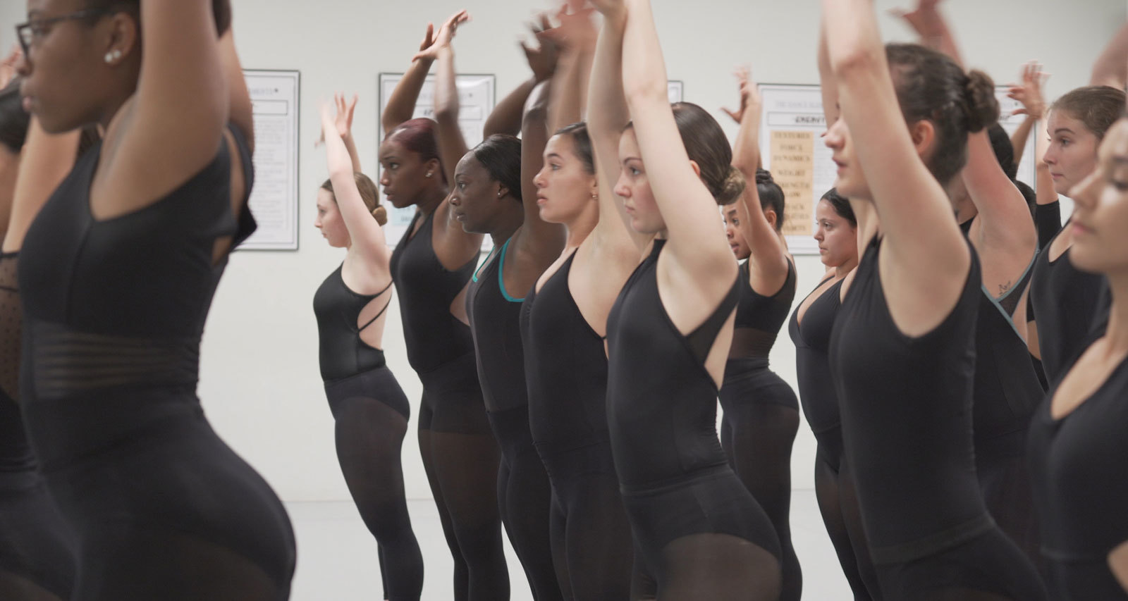 Miami Arts Dance students raise their arms high.